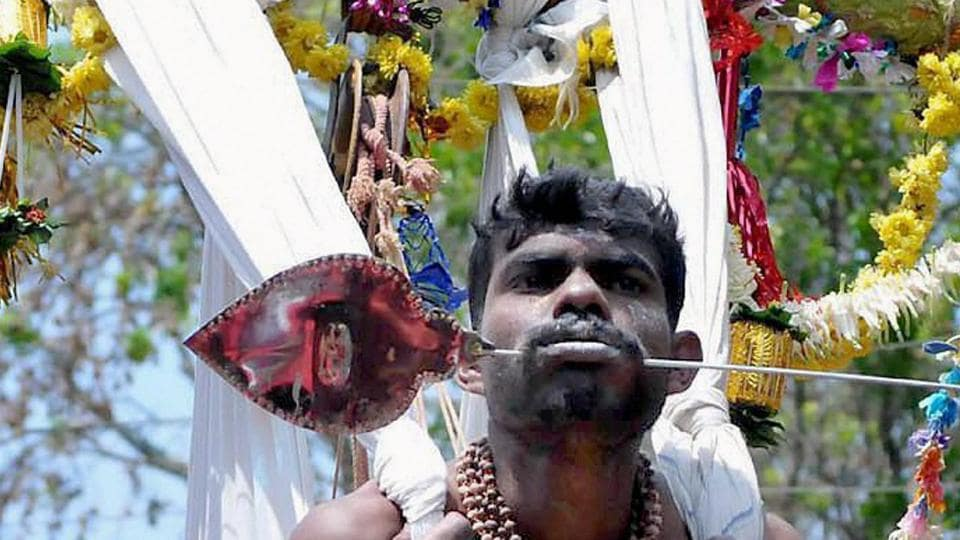 A Devotee pierced his mouth with iron rod as an offering on the occasion of Panguni Uthiram at Mallandur near Chikmagalur in Karnataka. (PTI)