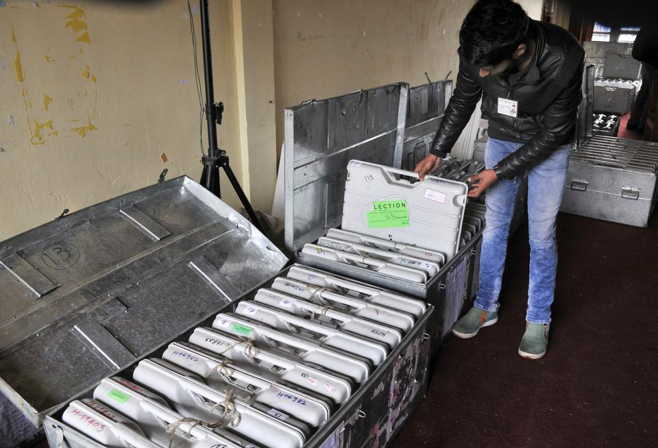 A government employee takes out electronic voting machines at a local school in Srinagar. (Waseem Andrabi / HT Photo)