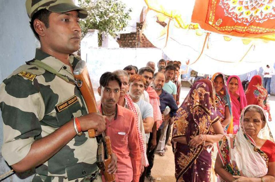 People queue up before polling booths in Dholpur on Sunday.