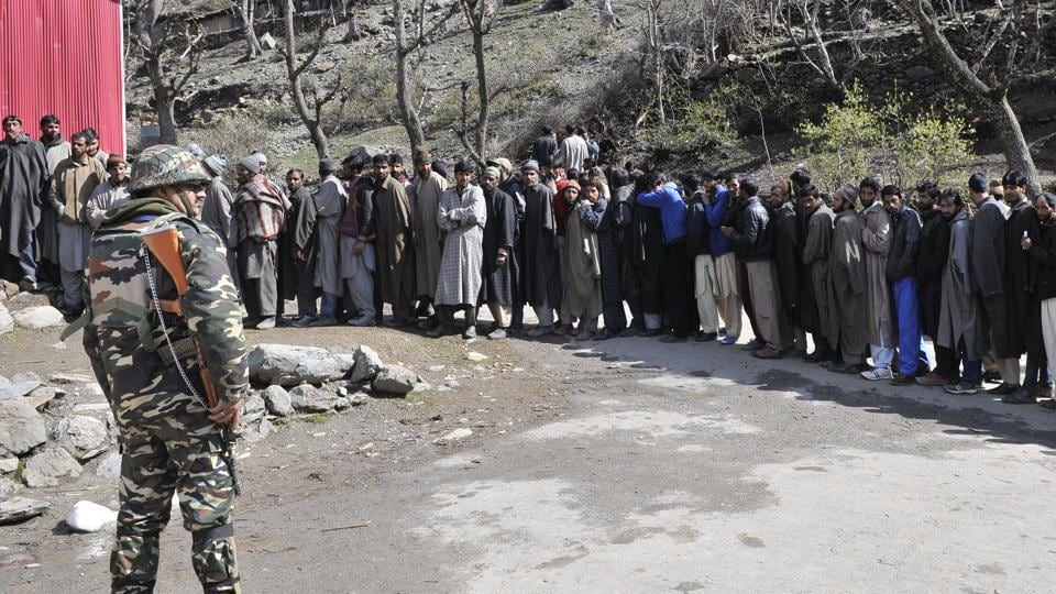 Members of Gujjar community stand in line as they wait their turn to cast their vote outside a polling station in Baba Nagri area in Kangan, some 50 km from Srinagar.