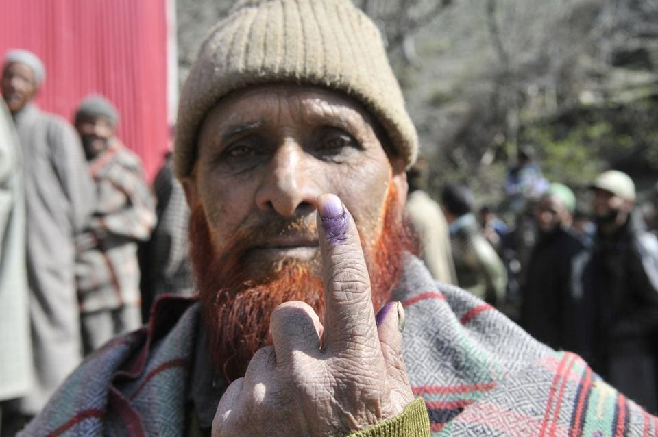 Member of Gujjar community shows his ink marked finger after casting vote,  outside a polling station in Baba Nagri area in Kangan, some 50 km from Srinagar.
