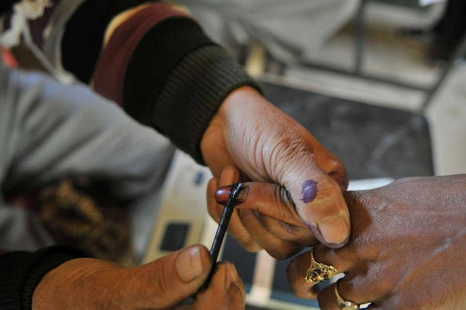 An election official marks the finger of a voter inside a polling station in Baba Nagri area in Kangan, some 50 km from Srinagar.