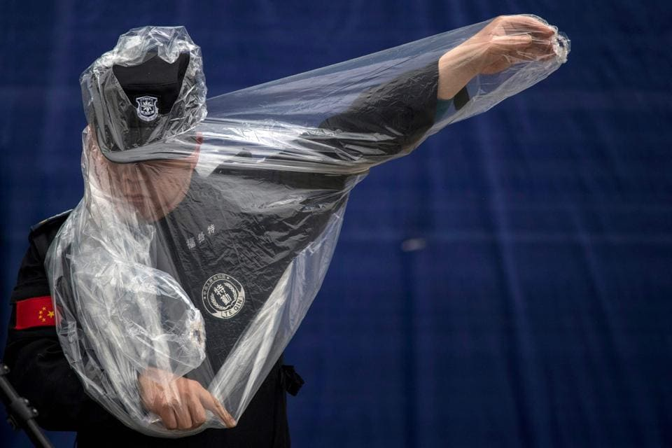 A security man puts on his rain jacket at the paddock in Shanghai on April 6, 2017, ahead of the Formula One Chinese Grand Prix. (Johannes EISELE / AFP)