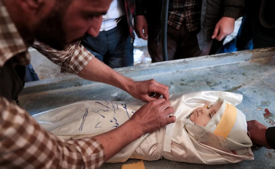 A Syrian wraps the burial shrowd of one-year-old infant Amira, whose body lies in a make-shift morgue, after she died in a reported air strike on the rebel-held town of Douma, on the eastern outskirts of the Syrian capital Damascus, on April 7, 2017. (Abd Doumany / AFP)