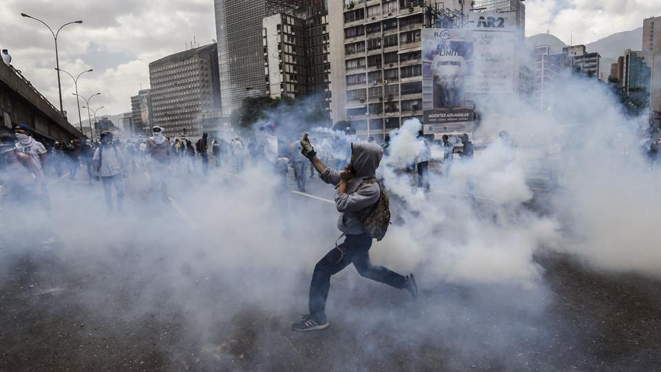 Venezuelan opposition activists react to tear gas shot by the police during protests against the government of President Nicolas Maduro on April 6, 2017 in Caracas. The center-right opposition vowed fresh street protests - after earlier unrest left dozens of people injured - to increase pressure on Maduro, whom they blame for the country's economic crisis. (JUAN BARRETO / AFP)