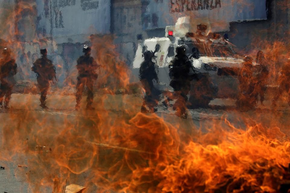 Venezuelan national guards walk behind a burning blockade during clashes with demonstrators during an opposition rally in Caracas, Venezuela, April 6, 2017. (Marco Bello  / REUTERS)