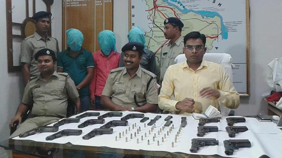 Police show seized pistols and ammunition in Murshidabad.