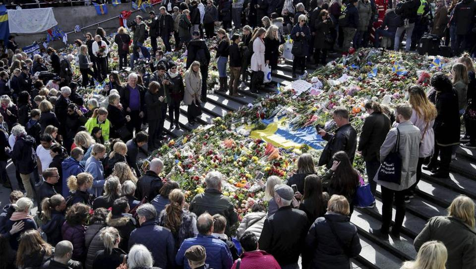People crowded around flowers near the department store Ahlens in Stockholm, Sweden, Sunday, April 9, 2017. A hijacked truck was driven into a crowd of pedestrians and crashed into a department store on Friday.