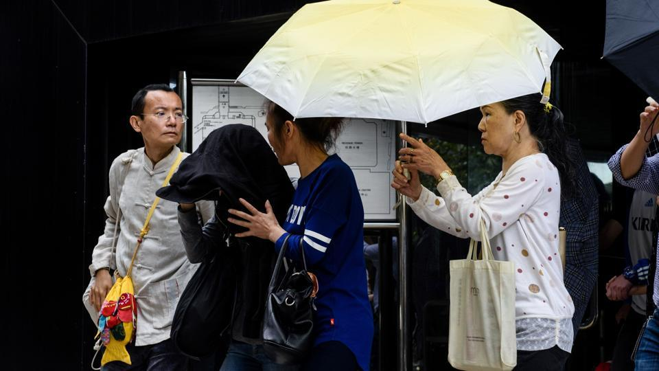 A group of people, including one (2nd L) with their face covered, leave the District Court after local technician Yeung Ka-lun (not pictured), 32, was jailed in Hong Kong on April 10 for his participation in anti-China protests in 2016.