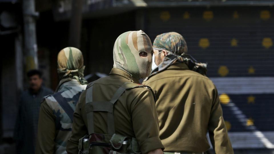 Masked policemen patrol at a closed market during a strike in Srinagar on Monday.