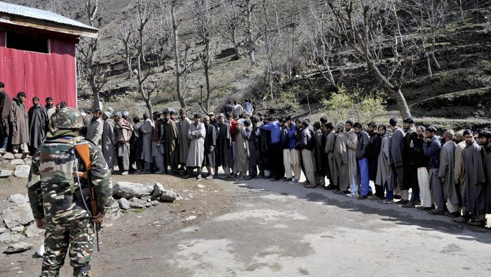 Voters stand in a queue to cast their votes at a polling booth in Srinagar on Sunday.