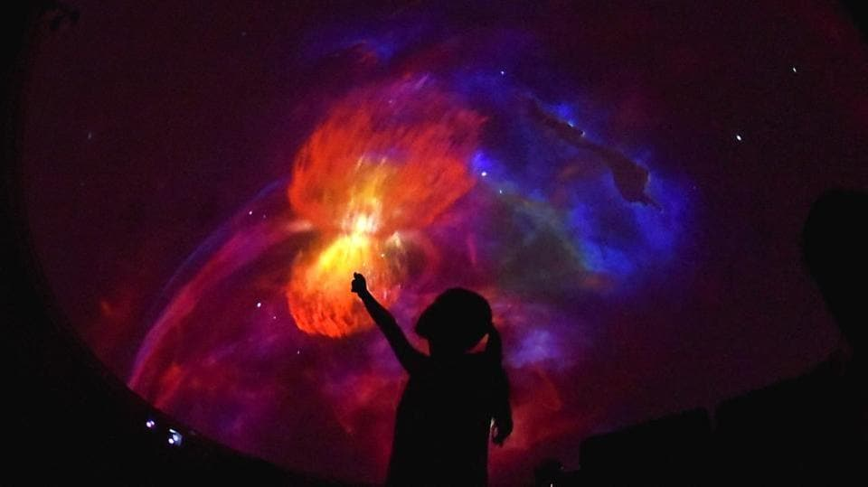 A student pointing out to a vivid display of colours during a screening at the Nehru planetarium sky theatre show in New Delhi. (Raj K Raj/HT PHOTO)