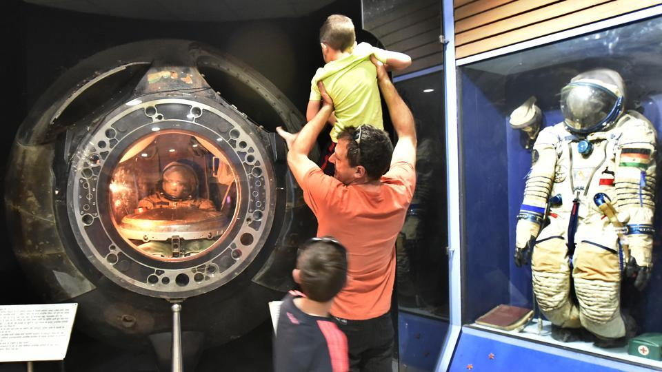 A man holds up a child looking into the Soyuz capsule spacecraft on display. The Soyuz space flight programme was initiated by the Soviet Union in the early 1960s to put a Soviet cosmonaut as part of a Moon landing project. (Raj K Raj/HT PHOTO)