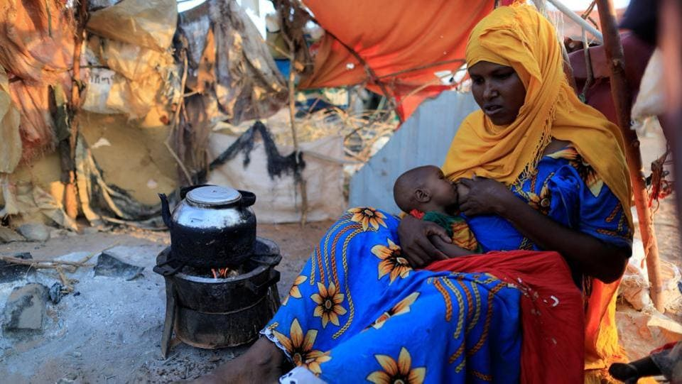Zeinab's sister Habiba, 29, feeds her baby as she sits beside a teapot at a camp for internally displaced people from drought hit areas in Dollow. The exchange, is typical of the choices facing Somali families after two years of poor rains. Crops withered and the white bones of livestock are scattered across the Horn of Africa nation. (Zohra Bensemra/REUTERS)