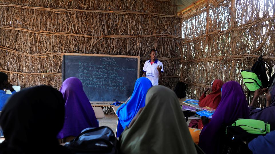 Zeinab's English teacher Abdiweli Mohammed Hersi teaches children at the school near a camp. Between them lie Somalia's parched sands and the swamps of oil-rich South Sudan, where starving families fleeing three years of civil war survive on water-lily roots. (Zohra Bensemra/REUTERS)