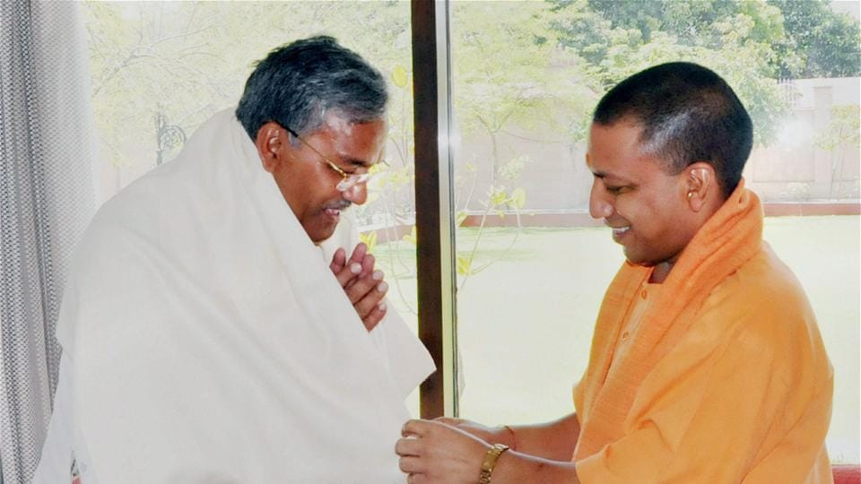 Uttar Pradesh chief minister Yogi Adityanath greets Uttarakhand chief minister TS Rawat at a meeting in Lucknow on Monday.