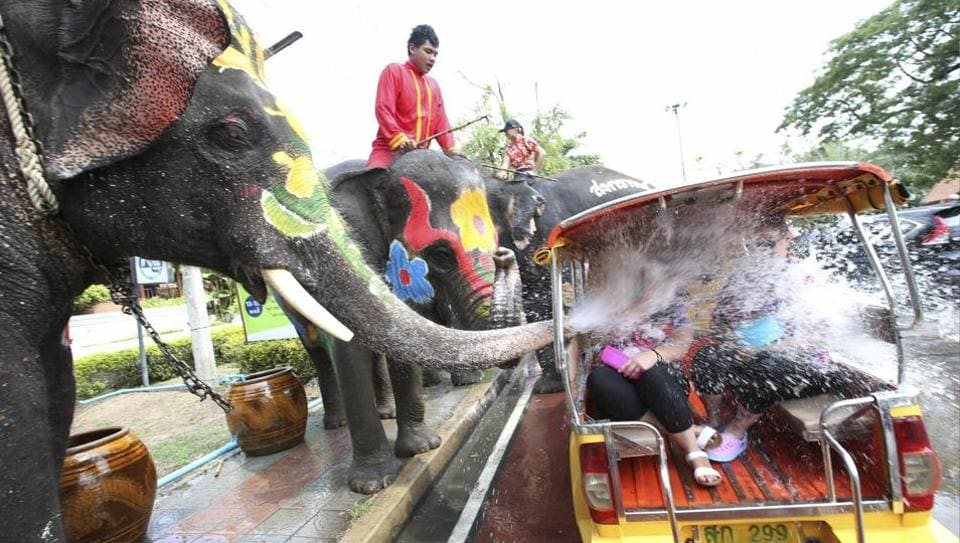 With assist from its mahouts, elephants blow water from its trunk  on motor-tricycle or Tuk Tuk at Songkran or ancient Thai New Year celebration . (AP)