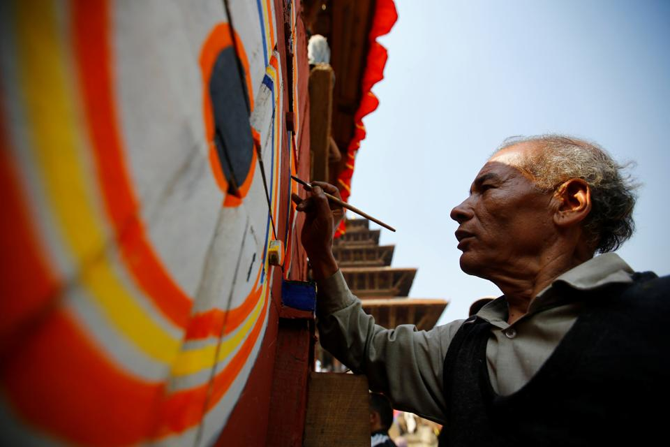 An artist paints on the giant wheel of the chariot of God Bhairab.  (Navesh Chitrakar/REUTERS)