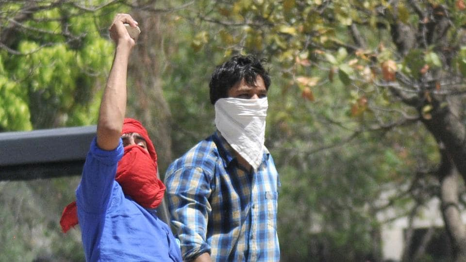 Students raising slogans and throwing stones at cops during a protest against fee hike at Panjab University in Chandigarh on Tuesday, April 11.