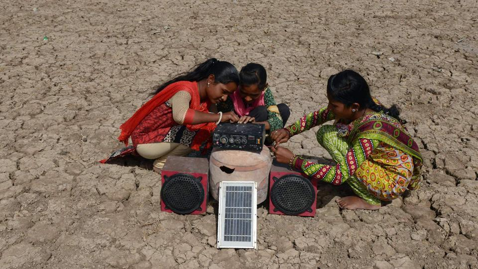 Puja Ganeshbhai Muladiya (R) along with her sisters prepare for a traditional Garba (Gujarat's folk dance) as they connect a solar panel-powered music systems in the Little Rann of Kutch. (AFP)