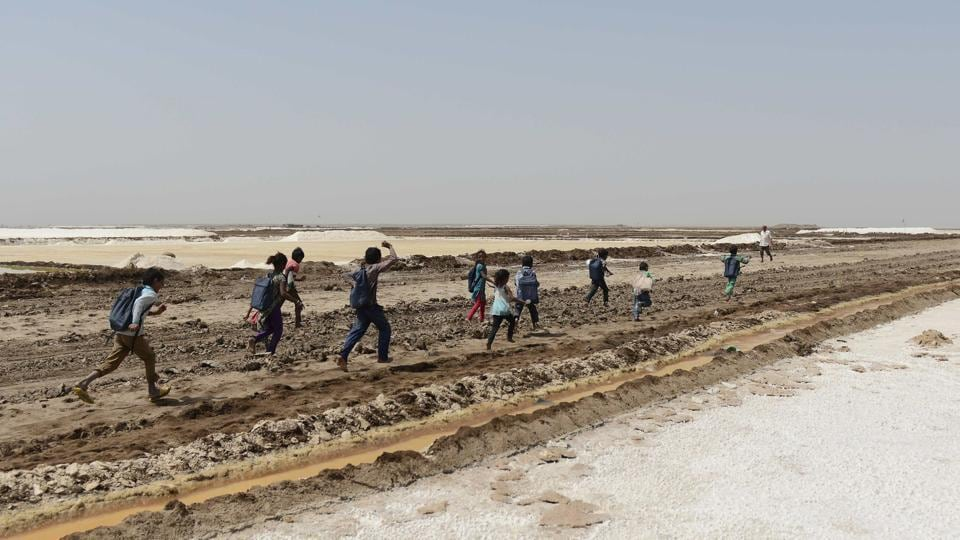 A group of children run as they finish a tent school workshop with the 'Zero Connect' programme, in the Little Rann of Kutch. They are part of some 10,000 families living on the inhospitable salt flats of western Gujarat, where their parents work eight months a year in extreme conditions. (AFP)
