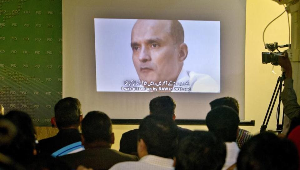 Pakistani journalists look at an image of Indian naval officer Kulbhushan Jadhav, who was arrested in March 2016, during a press conference in Islamabad.