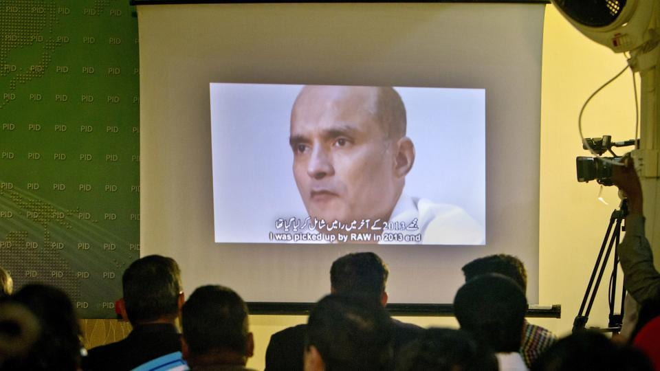 In this file photo, journalists look at an image of Indian naval officer Kulbhushan Jadhav, who was arrested in March 2016, during a press conference by Pakistan's army spokesman and the information minister, in Islamabad.