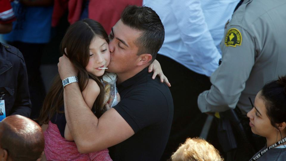 A student who was evacuated after a shooting at North Park Elementary School is embraced after groups of them were reunited with parents waiting at a high school in San Bernardino, California, U.S. A gunman entered an elementary school classroom in San Bernardino, California, and fatally shot his estranged wife, who was a teacher, and an eight-year-old student, before he killed himself, according to law enforcement. (Mario Anzuoni/REUTERS)