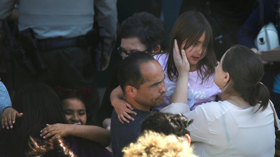 A student who was evacuated after a shooting at North Park Elementary School is embraced after groups of them were reunited with parents waiting at a high school in San Bernardino, California.