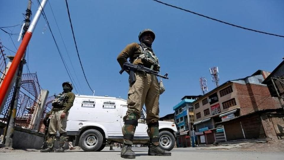 Policemen guard a deserted street during restrictions in downtown Srinagar.