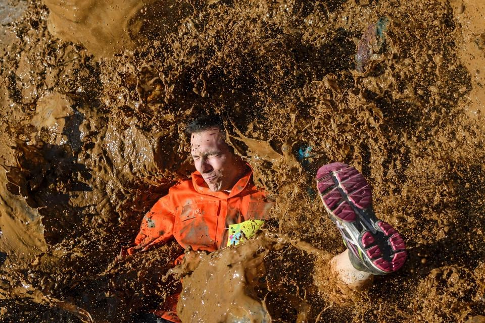 A competitor lands in mud as they take part in the 'Barjot Run' obstacle race in Biere, western Switzerland. (Fabrice Coffrini/ AFP)