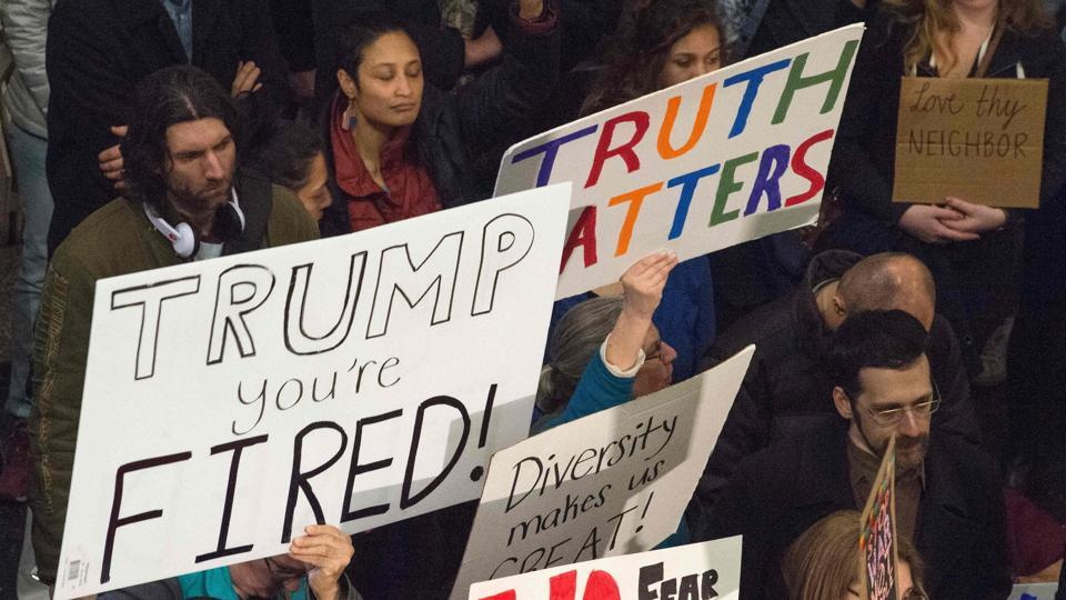 People hold up signs during a protest against US President Donald Trump's immigration rules at the Regan National Airport in Arlington.