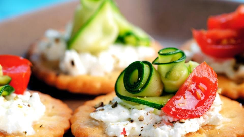 Bite-size canapes with sour cream, zucchini or cucumber and tomato.