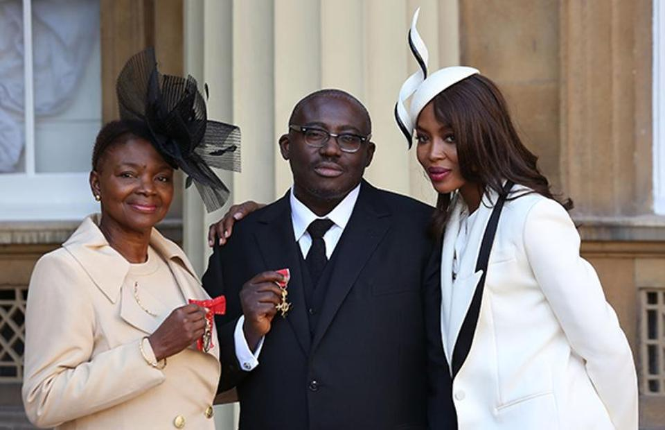 Fashion and style director of W magazine Edward Enninful (C) poses his insignia after being appointed an Officer of the Order of the British Empire.