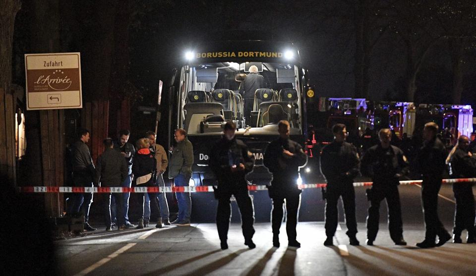 Police officers stand in front of Borussia Dortmund's damaged team bus after the explosions on Tuesday.