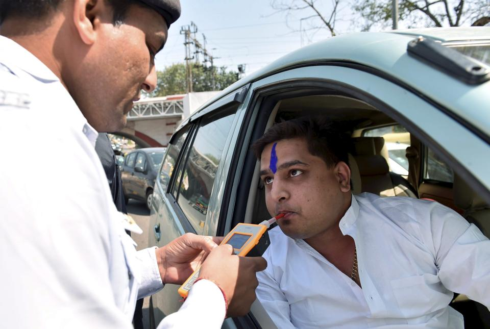 A policeman uses  a breath analyser on a driver  in New Delhi.  Once the new motor vehicles act is implemented, those in the habit of driving rashly or flouting rules should be prepared to pay as much as 20 times more than before.