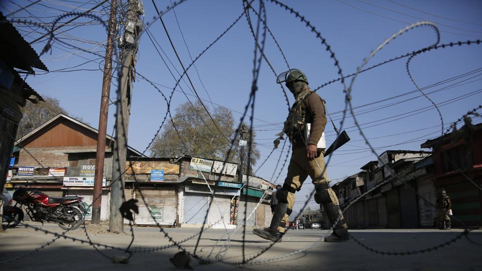 """A paramilitary soldier guards a check point during a strike in Srinagar on Monday. Three videos showing soldiers being assaulted and abused by mobs shouting """"India go back"""" have gone viral."""