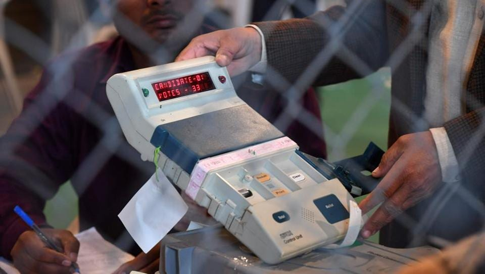 An election official shows an open Electronic Voting Machine (EVM) to political agents at a counting centre in Ghaziabad on March 11.