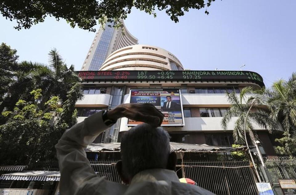 A man looks at a screen across the road displaying the Sensex on the facade of the Bombay Stock Exchange (BSE).