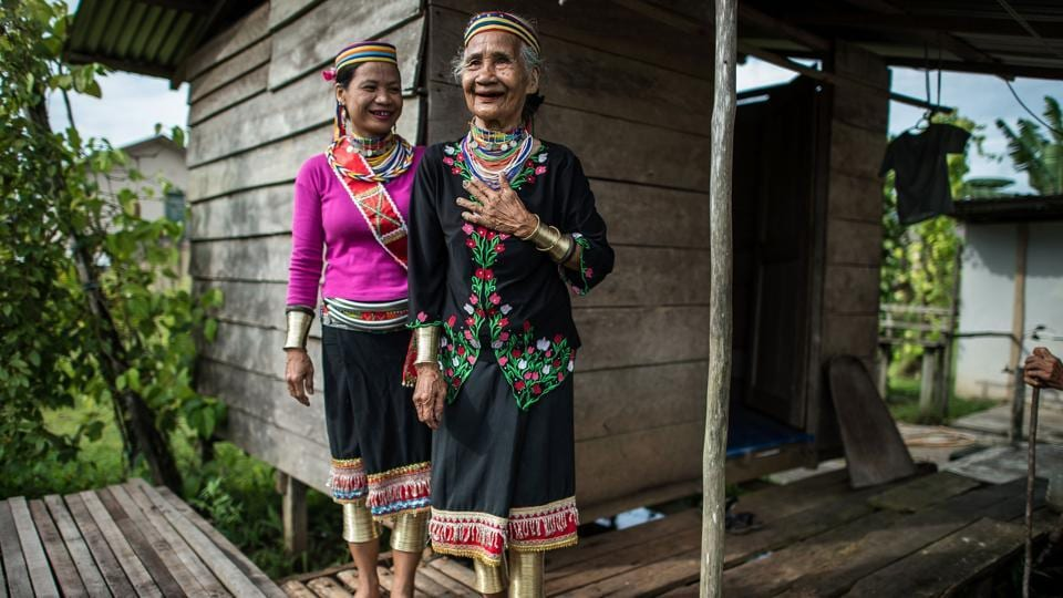 Anyu Daik (R), 70, and Anat Ugom, 44 (L), from a sub-tribe of the Bidayuhs indigenous group wearing traditional yellow copper rings called 'rasung' on their calves, ' ruyang' on their forearms and 'tumbih' as necklaces as they stand outside their kitchen in Padawan in the state of Sarawak on the island of Borneo.  (Mohd RASFAN / AFP)
