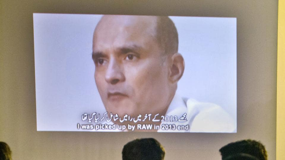 In this file photo, journalists look at an image of former Indian naval officer Kulbhushan Jadhav during a press conference.