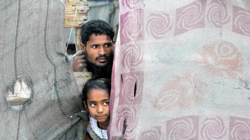 A Rohingya Muslim along with his daughter peeps from a damaged door at a refugee camp. J&K has several charities that help the Rohingya Muslims.13,400 Myanmarese and Bangladeshi migrants are living in camps in Jammu and Samba.  (Nitin Kanotra/HT Photo)