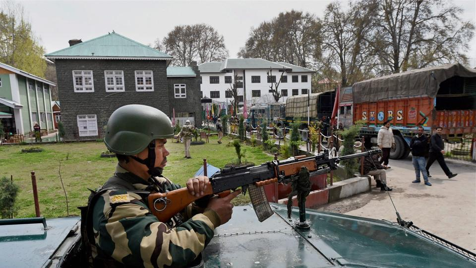 A soldier stands guard atop an armoured vehicle outside an EVM-distribution centre in a school, before elections to Srinagar Lok Sabha seat, in Srinagar.