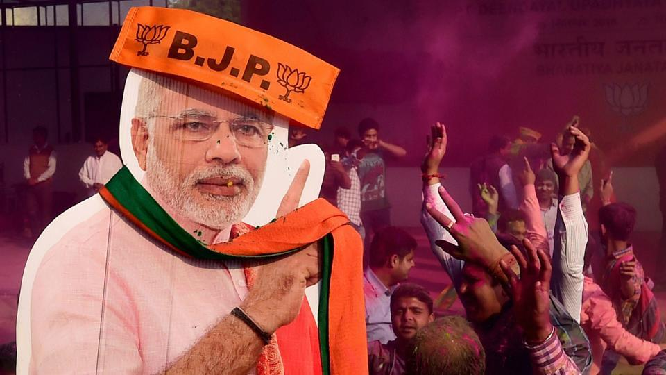 BJP workers play holi with a giant cut-out of Prime Minister Narendra Modi as they celebrate the party's victory in the UP and Uttarakhand Assembly elections, at the party headquarters in New Delhi on March 11.