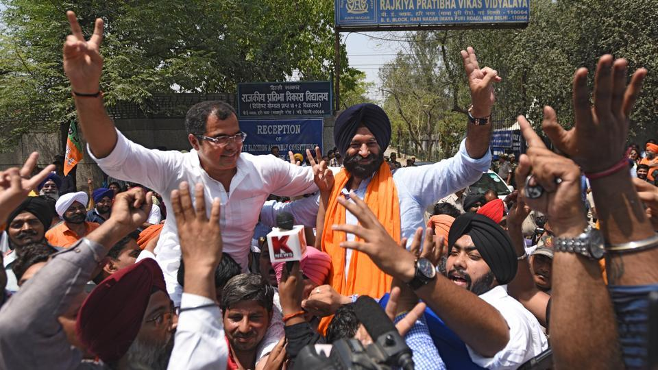 BJP's winning candidate Majinder Singh Sirsa celebrates his victory with supporters in Rajouri Garden in New Delhi on Thursday.