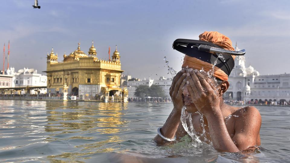 Devotee take a holy dip in the sarover (water tank) at the Golden Temple in Amritsar  to mark Baisakhi festival. (Gurpreet Singh/ HT Photo)