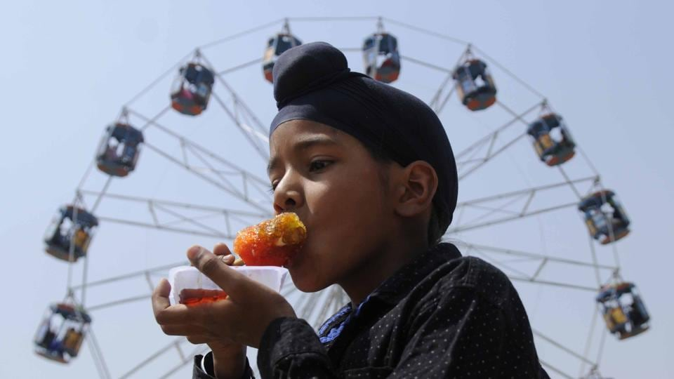 A boy enjoys ice candy during the Baisakhi mela at Gurdwara Bahadurgarh Sahib near Patiala on Thursday. (Bharat Bhushan/HT)