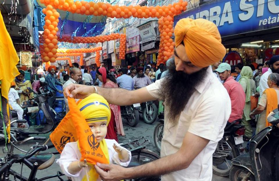 A shopkeeper decorating a dummy in traditional Sikh attire outside his shop in Patiala on Thursday. (Bharat Bhushan/HT)