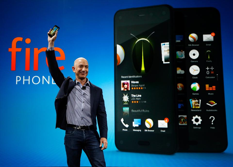 Amazon CEO Jeff Bezos holds up the new Amazon Fire Phone at a launch even.