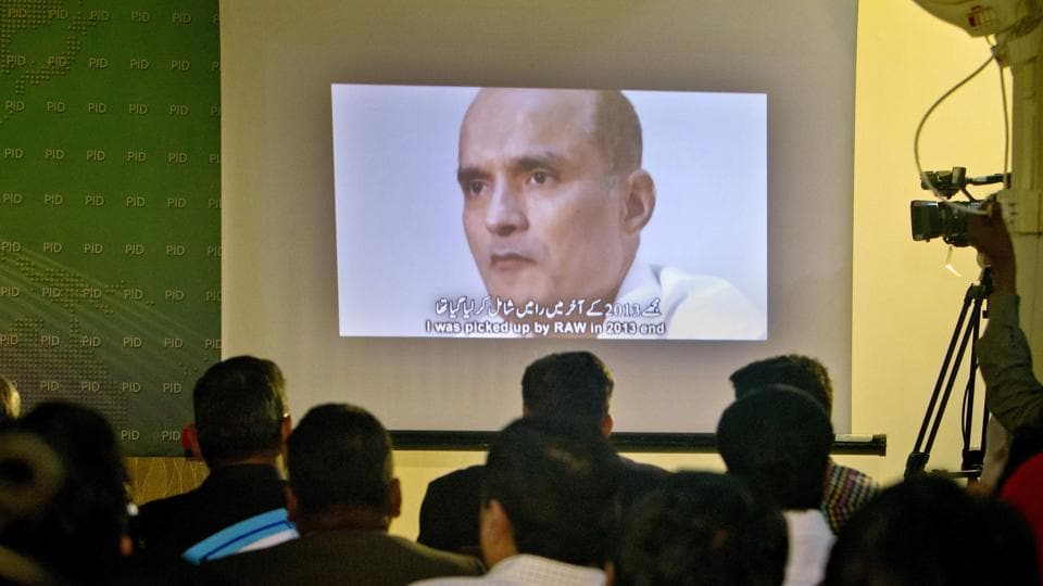 In this March 29, 2016 photo, journalists look an image of Indian naval officer Kulbhushan Jadhav, who was arrested in March 2016, during a press conference by Pakistan's army spokesman and the Information Minister, in Islamabad, Pakistan.